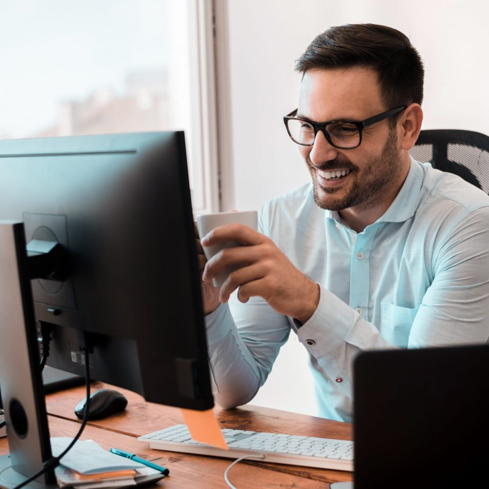 Smiling businessman holding coffee cup while working at desk in home office